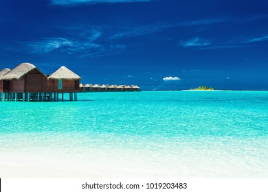 Over water bungalows with steps into lagoon, tropical Maldives