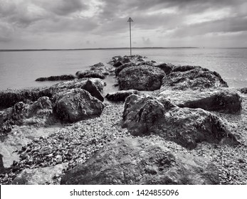 Over wet, seaweed covered rocks and out in the the Solent estuary on a dark cloudy day in spring.