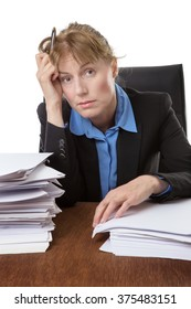 Over worked woman, rests her head on her hand, surrounded by big piles of paperwork.