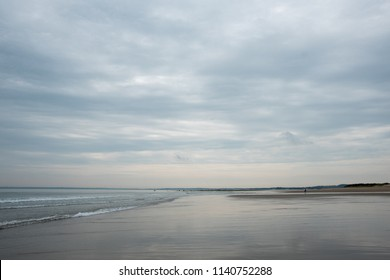 Overcast beach Plum Island MA seascape. Sky fills 2/3 of image, blue grey with warm tones at horizon. Sand is on right with water line cutting diagonal from middle to left.