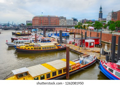 Overcast skyline of Hamburg harbor with moored touristic boats by the piers, freight cranes of industrial shipping city port on background, Germany