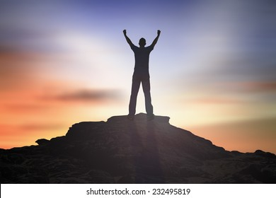 Overcome concept: Silhouette of man raised hands at mountain sunset background,