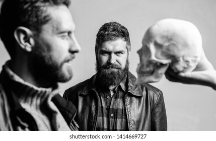 Overcome your fears. Be brave. Focused on breaking fear. Psychology concept. Human fears and courage. Looking deep into eyes of your fear. Man brutal bearded hipster looking at skull symbol of death.