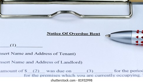 An overdue rent form on a metal clipboard with a ball point pen ready for you to sign, to try and receive your legal rent entitlement.