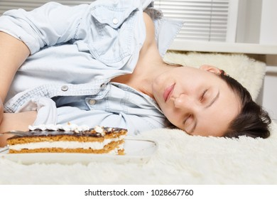 overeat young woman with sweet cake lying on bed