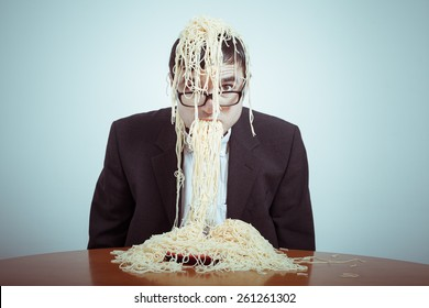 Overeating and consumerism concept. Nasty businessman eating pasta.