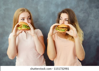 Overeating, greed, gluttony, bulimia, fast-food, diet, enjoyment, treat, appetite, hunger. Two cute young women engorging delicious burgers and suspiciously look at each other