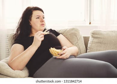 overeating, sedentary lifestyle, bad habits, food addiction, eating disorders. fat overweight woman lay on the coach with junk food. depression, laziness
