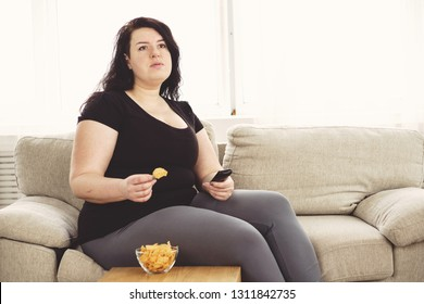 overeating, sedentary lifestyle, bad habits, food addiction, eating disorders. fat overweight woman lay on the coach with tv remote and junk food. depression, laziness