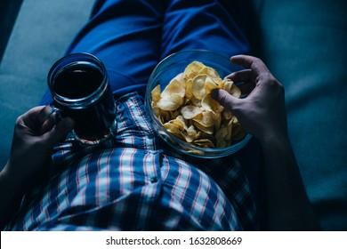 overeating, sedentary lifestyle, bad habits, food addiction, eating disorders. fat overweight man lay on the coach with tv remote, junk food and beer. depression, laziness alcohol addiction