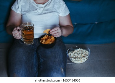 overeating, sedentary lifestyle, bad habits, food addiction, eating disorders. fat overweight woman lay on the coach watching tv, with junk food and beer. depression, laziness alcohol addiction