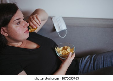 Overeating, sedentary lifestyle, bad habits, food addiction, eating disorders. Fat overweight woman lay on the coach with junk food. New normal, social distance, quarantine lockdown concept