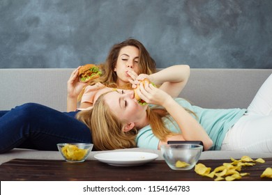 Overeating, sedentary lifestyle, fast-food, laziness, pleasure, delight, enjoyment, appetite, hunger. Two young lazy women lying at coach enjoy eating burgers and chips