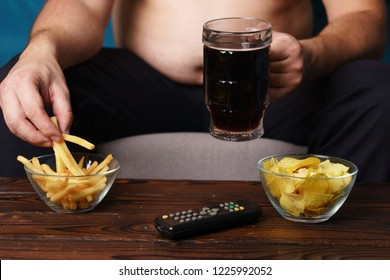overeating, sedentary lifestyle, hormonal disorder, alcohol addiction, bad habits. fat overweight man sitting on the sofa with tv remote, eat junk food and drink beer