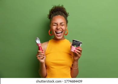 Overemotive cheerful dark skinned teenage girl laughs out loudly, has fun and eats delcious frozen dessert, holds cup of ice cream and spoon, dressed in bright yellow clothes, expresses happiness