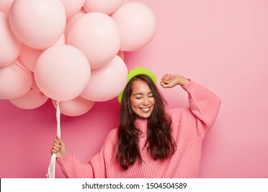Overemotive chilling woman with cheerful expression, raises hand, dances to music, has fun at party, holds balloons, has happy mood during her birthday. Asian girl celebrates getting new job