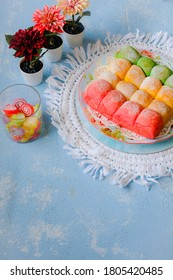 Overexposed Bright Mood of Colorful Soft zmilk Bread Candy and Flowers on a blue white grainy table