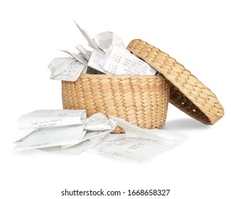 Overfilled storage basket of receipts for filing taxes and deductibles. Straw basket with many crumbled receipts in and around the container. Isolated on white.