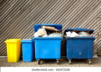overfilled trash of large wheelie bins for rubbish, recycling and garden waste