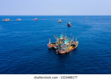 Overfishing - aerial view of a large fleet of fishing trawlers working together in a small area of the Andaman Sea