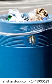 Overflowing blue metal public waste bin with plastic liner