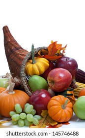 An overflowing cornucopia including pumpkins, grapes, gourds and leaves on a white background