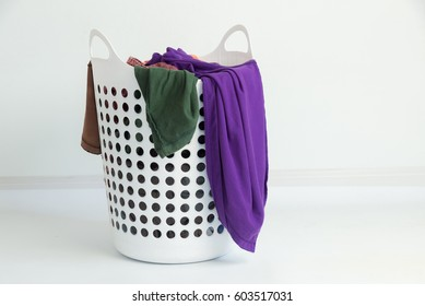 Overflowing laundry basket on white ground. Household chore concept.