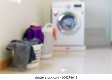 Overflowing laundry basket with washing machine. Household chore concept.Blurred Effect.