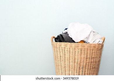 Overflowing laundry wicker basket. Household chore concept on gray background