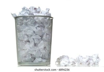An overflowing waste basket full of crumpled pieced of paper