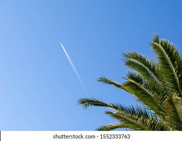 Сontrail of overflying passenger airplane in the clear blue sky