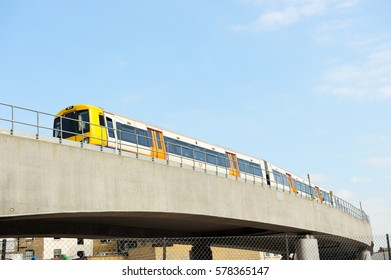 Overground Train moving slowly on the upper track with blue sky background in Shoreditch, London, England