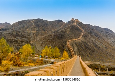 Overhanging Great Wall in Jiayuguan, China. The west end of the Great Wall of China in Autumn. The Great Wall appears very like a dragon overhanging the slope.