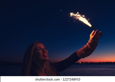 Overhappy woman holding burning roman candle in her hand raised up in the night sky
