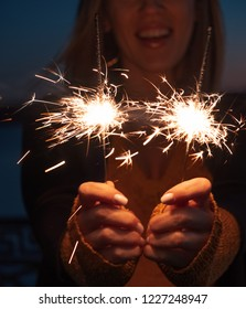 Overhappy woman holding burning sparklers in her hands close-up shot in warm colors