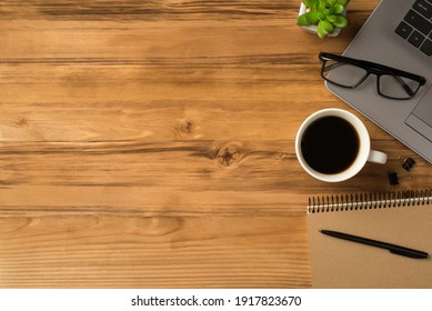 Overhead above close up view photo picture of laptop notebook keyboard cup of beverage binder clips spiral kraft notepad with pen isolated brown backdrop with blank place