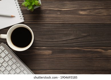 Overhead above view photo of coffee copybook succulent green plant keyboard on dark textured backdrop