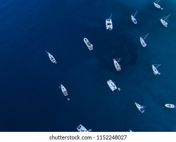 Overhead aerial image of anchored sailboats and catamaran in shallow clear waters