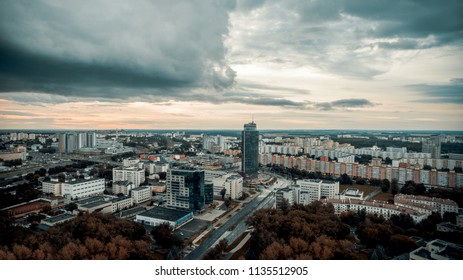 Overhead aerial view of the evening cityscape panorama with stormy weather. Drone shoot with dark sky with beautiful clouds. Flying over Minsk city.