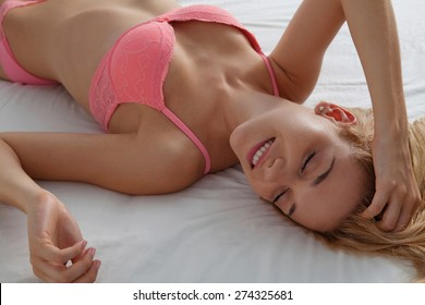 Overhead beauty portrait of young woman laying relaxing on a luxury bed in a home bedroom, smiling flirting wearing sexy pink bra lingerie indoors. Home lifestyle and skin hair care, interior.