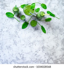 Overhead border still life of green smoothie in glass and sorrel leaves on white textured background. Healthy lifestyle concept