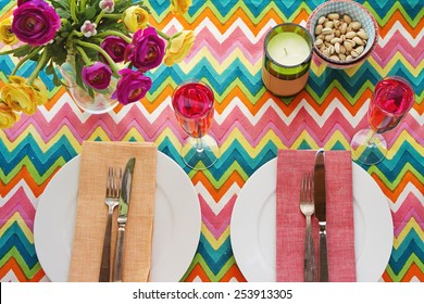 Overhead Bright colorful table setting with multi-colored chevron pattern tablecloth
