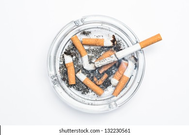 Overhead of burning cigarette in ashtray on white background