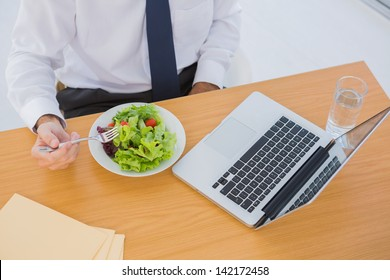 Overhead of a businessman eating a salad on his desk during the lunch time