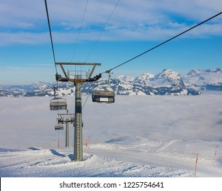 An overhead cable car, summits of the Alps rising from sea of fog - a wintertime view from the Fronalpstock mountain in the Swiss canton of Schwyz.