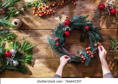 Overhead. Christmas time. On the wooden table, woman's hands make a crown for the festive season. branches of fir, berries, balls and rope to decorate it