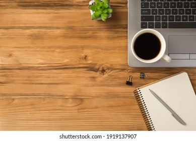 Overhead close up above flat lay view photo of laptop keyboard with mug of beverage green succulent and clear spiral copybook isolated brown loft backdrop with blank space