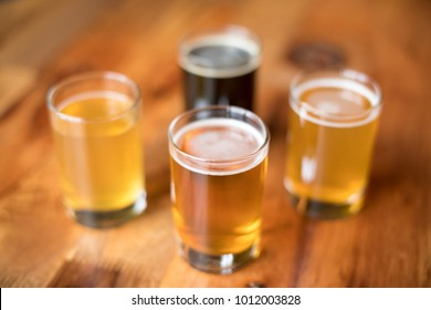 Overhead close up on a flight of four craft beers in small pint glasses, at a local brewery