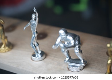 Overhead close up on a shelf of small athletic trophy figurines, with a silver plated baseball outfielder, for a fielding award