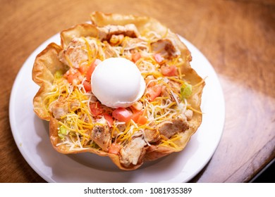 Overhead close up on a taco salad in a fried tortilla bowl with chicken and topped with sour cream